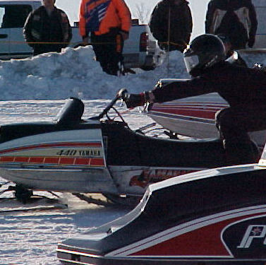Two snowmobiles compete in an oval ice race.