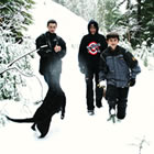 A mother and her three kids walking with a dog through the snow.
