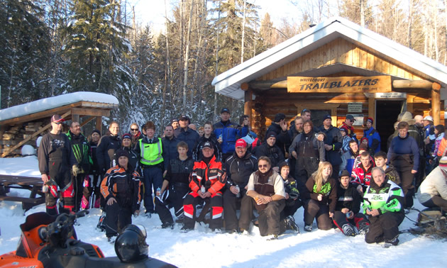 A big group of sledders gathered in front of a snowmobile cabin.
