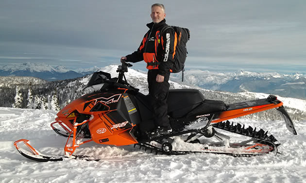 A man standing on an orange Arctic Cat in the backcountry.