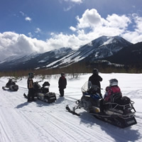 A group of snowmobilers parked alongside a trail.