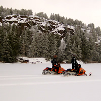 Two snowmobilers looking at a rocky outcropping.