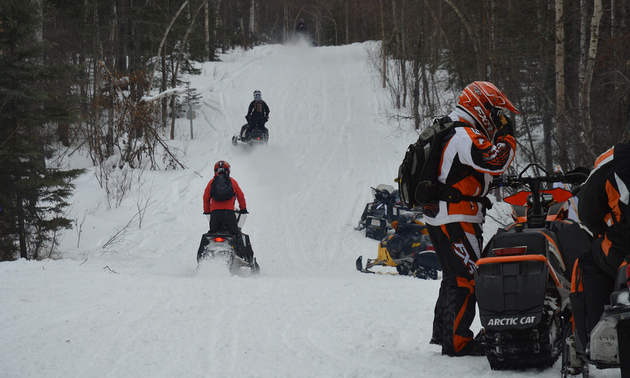 people on a snowmobile trail ready to ride