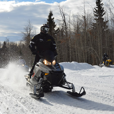 A snowmobiler on a Polaris RMK riding up Whitecourt trails.