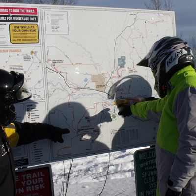 A group of snowmobilers looking at a billboard of snowmobile trail map in Whitecourt, Alberta.