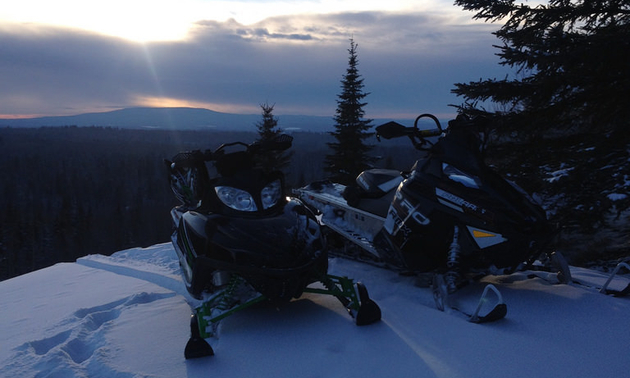 Tyler Ramstead sent in this postcard-worthy photo from one of his snowmobile outings in Whitecourt. It shows two sleds parked on a bluff overlooking a valley during sunset.