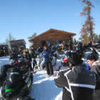 snowmobilers gathered in front of a cabin