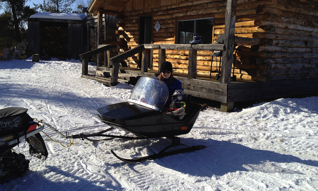 Mother and child in a snowmobile tobaggan