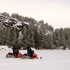 Two sleds riding in Whiteshell.  There is a rocky hill behind them and they are riding through a large open meadow.