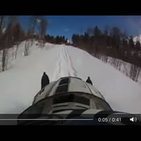 A person on a snowmobile riding along a trail.