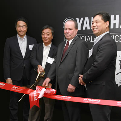 Yamaha officials cutting a red ribbon.