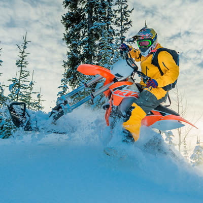 A man riding a KTM with a Yeti snow bike conversion kit on it.