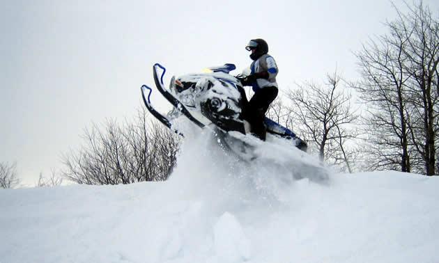 A snowmobiler jumping a drift in Saskatchewan.
